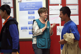 Deb Boyce of Catholic Charities greets guests to the Humanitarian Respite Center