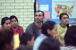 Immigrants hear a presentation by Sr. Norma Pimentel