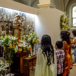 family praying by St. Anthony statue