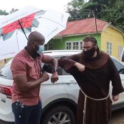 Friar and technician bump elbows