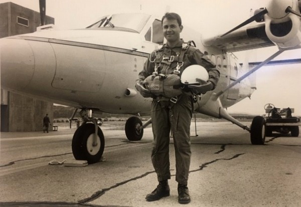 Fr Bob standing by airplane