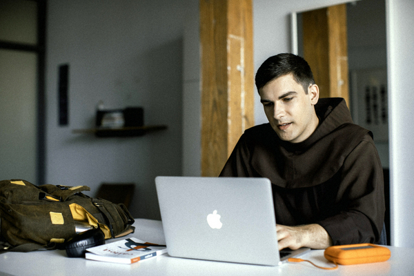 Friar in habit with laptop