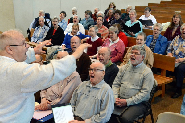 Fr. Fred Link, OFM, leads the choir practice for the 'Wake Up the World' concert celebrating consecrated life.