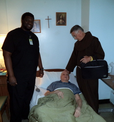 Fr. Simeon is comforted by Br. Norbert and his caregiver