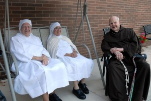 Fr. Cyprian Berens, OFM, sits with two nuns of the Little Sisters of the Poor