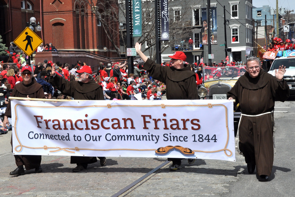 Br. Kenn Beetz, OFM, Fr. Jeff Scheeler, OFM, Fr. Al Hirt, OFM, and Br. Gene Mayer, OFM, take turns carrying the banner in the Reds Findlay Market Opening Day Parade.