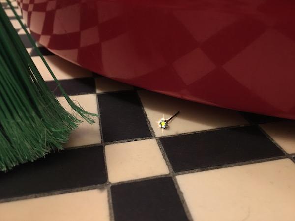 diamond earring on tile floor