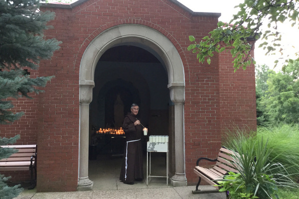 Br. Norbert Bertram lights a candle at the entrance to the outdoor grotto at the Shrine