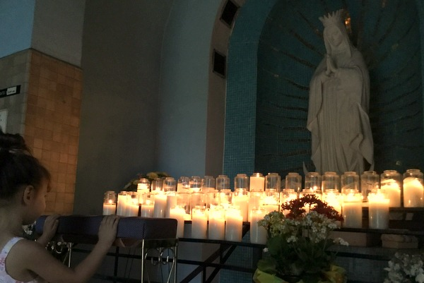 girl praying to OLO Guadalupe statue with candles
