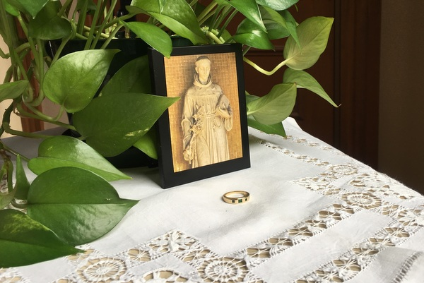 St. Anthony image and ring on table