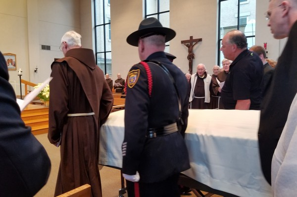 police and friars with casket