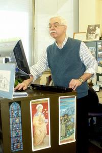 Fr. Pat McCloskey, OFM, stands at his computer at Franciscan Media