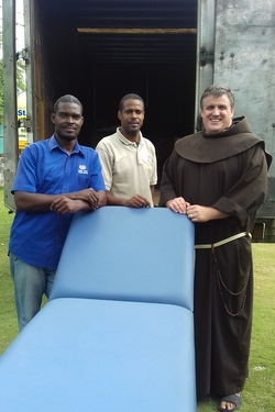 Friar and 2 men carry hospital bed
