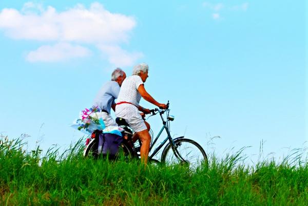 couple biking near grass and blue sky