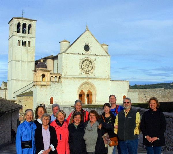 Pilgrims stand in front of the Basilica of Saint Francis in Assisi, Italy