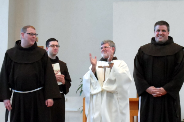Br. Michael Charron, OFM, (left) and Br. Colin King, OFM (right) receive applauds from Provincial Minister Fr. Jeff Scheeler, OFM, and Br. Adam Farkas, OFM