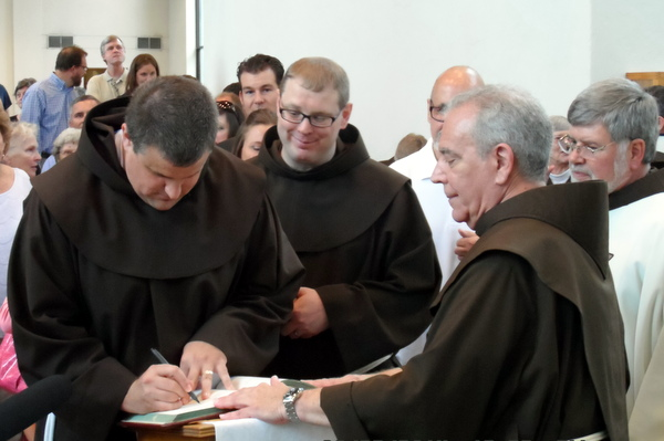 Br. Colin and Br. Michael sign the Book of Life held open by Fr. Dan Anderson, OFM