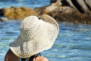 woman in sun hat by water